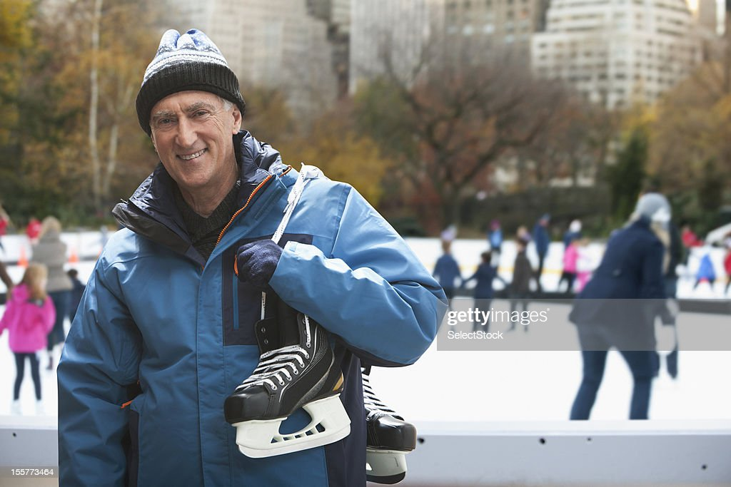 Senior man holding ice skates : Stock Photo