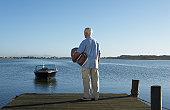 Senior man holding model boat on jetty, rear view