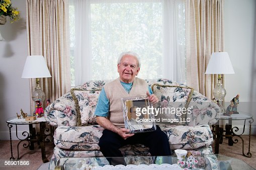 Senior man holding photograph : Stock Photo