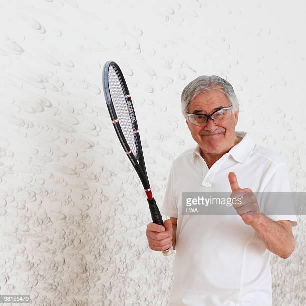 Senior Man Holding Racquet, By Squash Court Wall