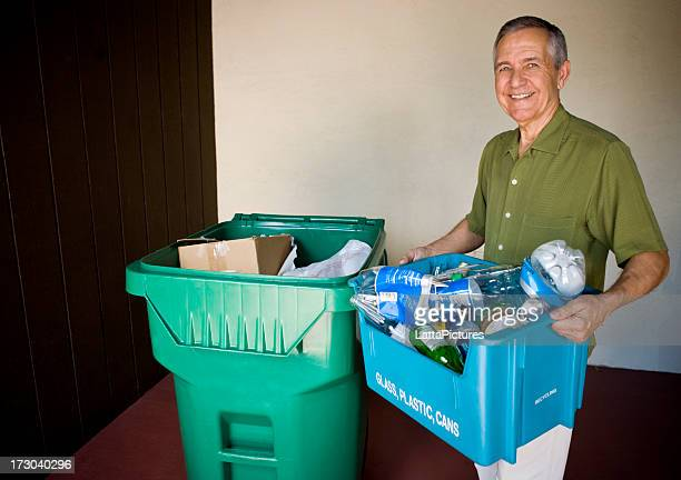 Senior man holding recycling bin with trash