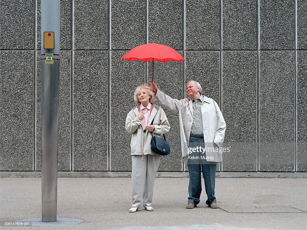 Senior man holding red umbrella over woman, standing on pavement