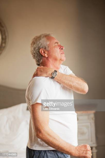 Senior man holding shoulder in pain