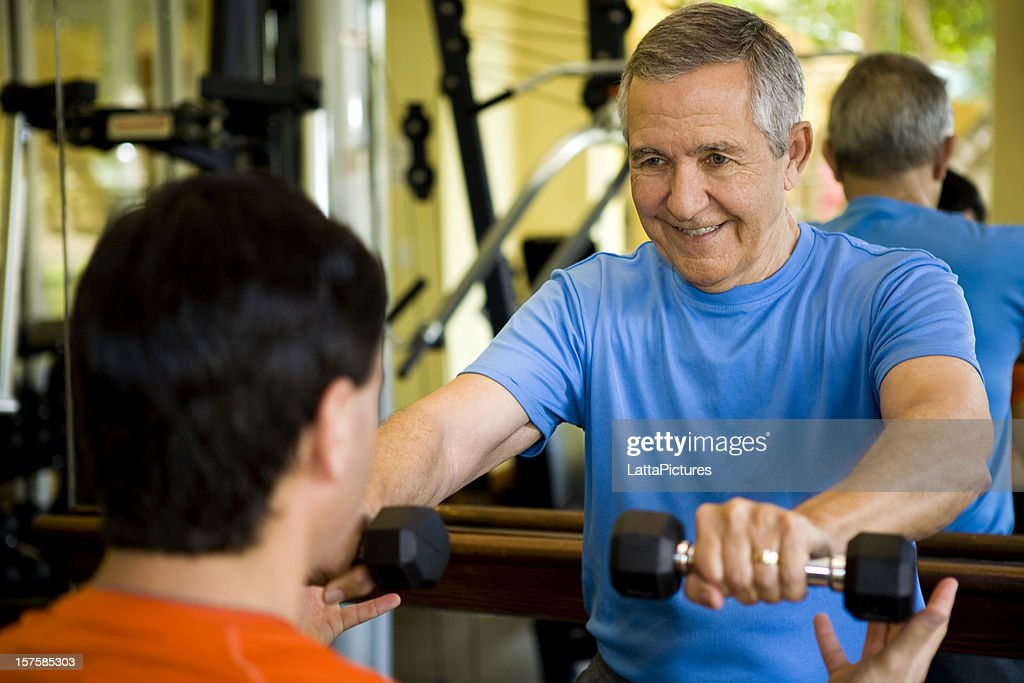Senior man working with personal trainer : Stock Photo