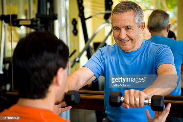 Senior man holding weights with personal trainer