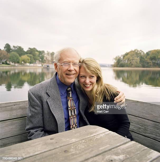 Senior man hugging adult daughter, lake in background