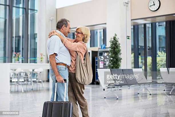 Senior man hugging his wife on arrival to airport
