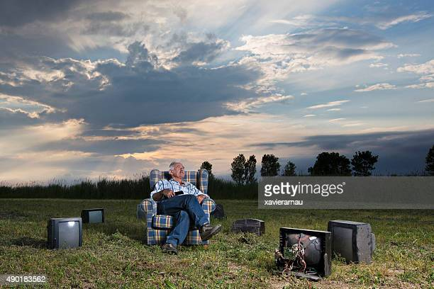 Senior man in a field surrounded by televisions