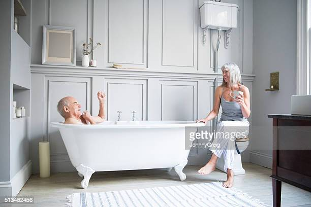 Senior man in bath talking to wife in hotel bathroom
