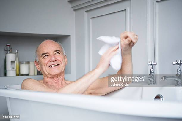 Senior man in bath washing himself smiling
