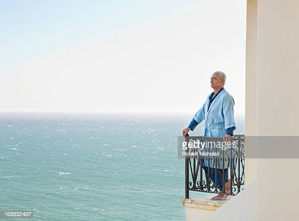 Senior man in bathrobe on balcony overlooking ocean