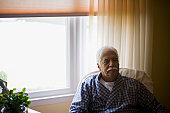 Senior man in bathrobe sitting in armchair by window, portrait
