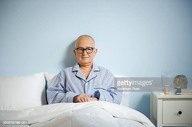 Senior man in bed, prescription medication on night table
