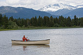 Senior man in canoe on river, mountain range in background