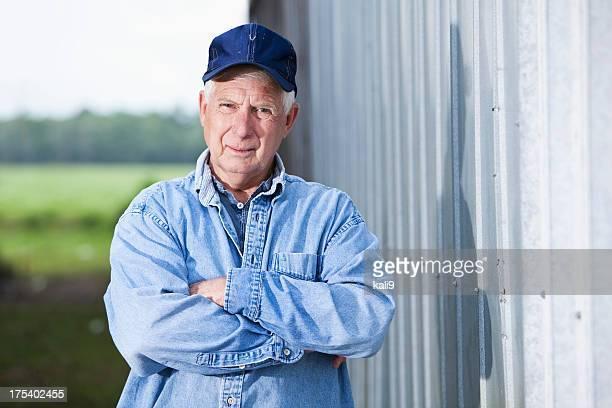 Senior man in cap standing  outside building