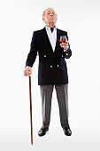 Senior man in captain's jacket with cane and brandy, portrait