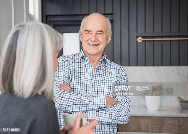 Senior man in checked shirt talking and smiling with wife