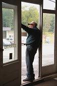 Senior man in doorway of store, looking out