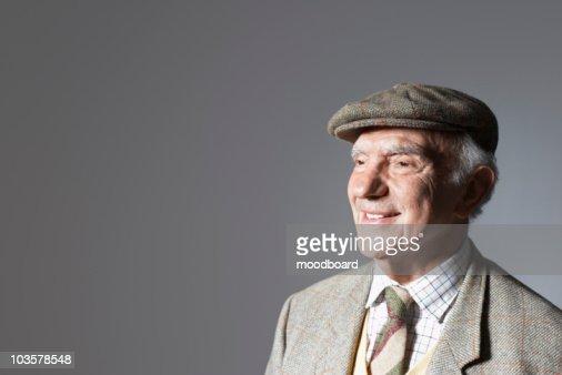 Senior man in flat cap, head and shoulders, in studio