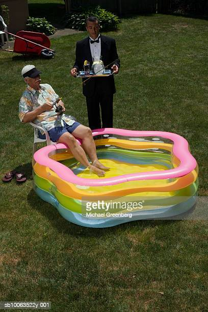 Senior man in garden with feet in inflatable pool, fishing, butler standing alongside with tray