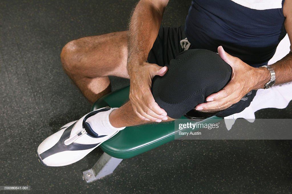 Senior man in gym wearing knee strap, lifting knee, overhead view