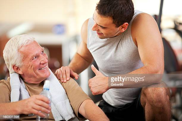 Senior man in gym with personal trainer