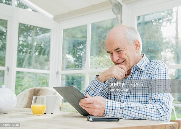 Senior man in his 70s using a digital tablet, smiling