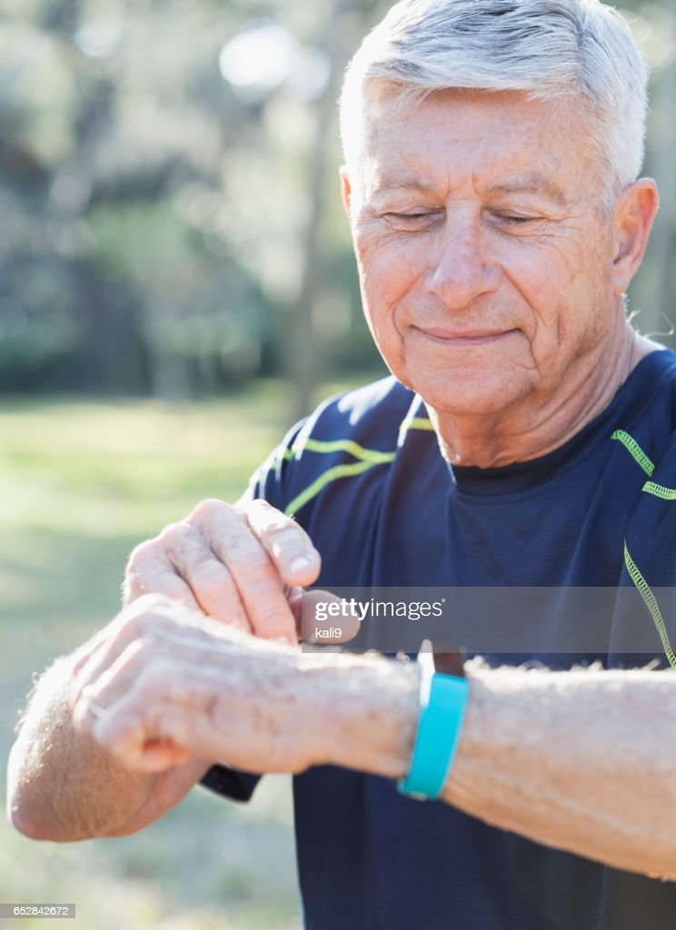 Senior man in his 70s using fitness tracker : Stock Photo