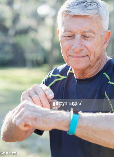 Senior man in his 70s using fitness tracker