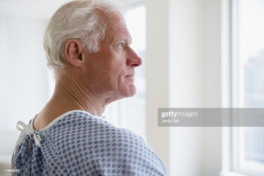 Senior man in hospital gown looking out the window