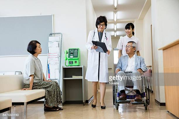 senior man in hospital with female doctor, woman and nurse