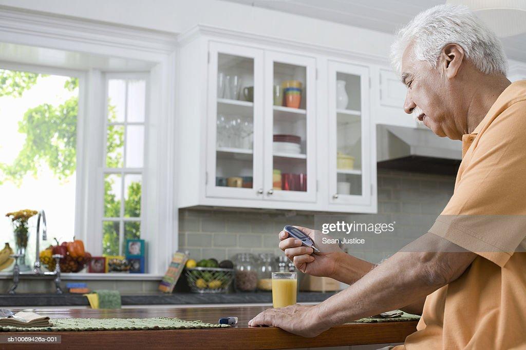 Senior man in kitchen, checking blood sugar levels