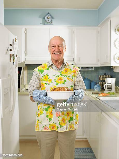 Senior man in kitchen,  holding dish with roasted chicken