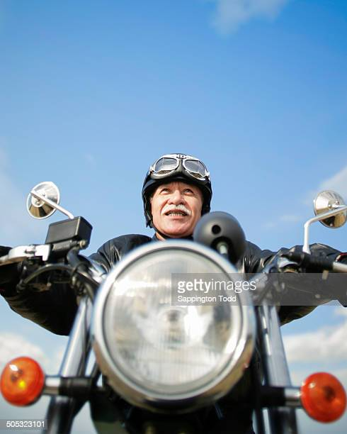 Senior Man In Leather Jacket Riding Motorcycle