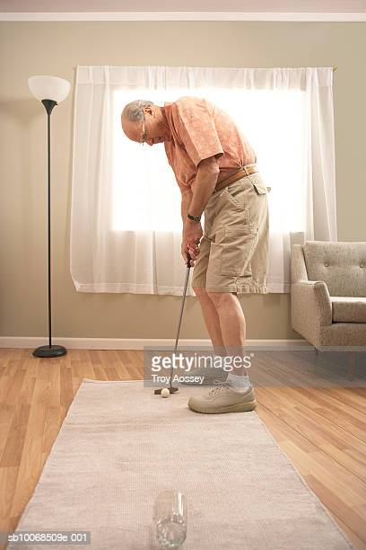Senior man in living room playing golf, putting into glass, side view