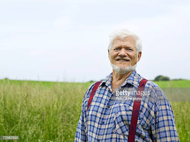 Senior man in long grass, smiling, portrait