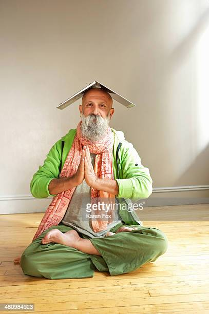 Senior man in lotus position with laptop on head