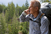Senior man in mountains talking on mobile phone, smiling