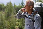 Senior man in mountains talking on mobile phone, smiling