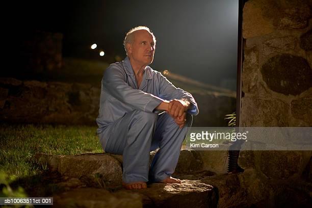 Senior man in pyjamas sitting outside house at night