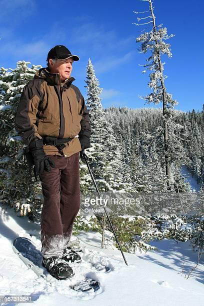 Senior hombre de senderos para realizar caminatas con raquetas para Loking a la vista