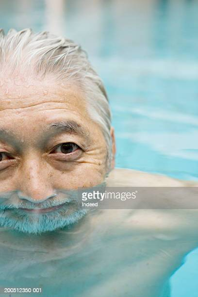 Senior man in swimming pool, with half of face underwater, close-up
