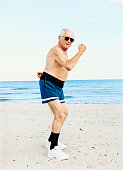 Senior Man in Swimming Trunks Stands on the Beach Flexing His Muscles