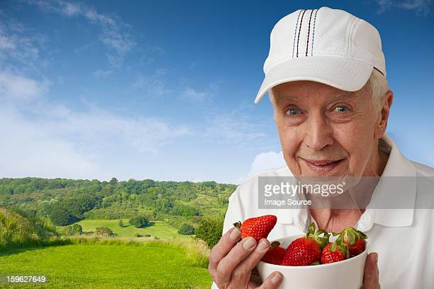 Senior man in tennis clothes with strawberries against rural scene