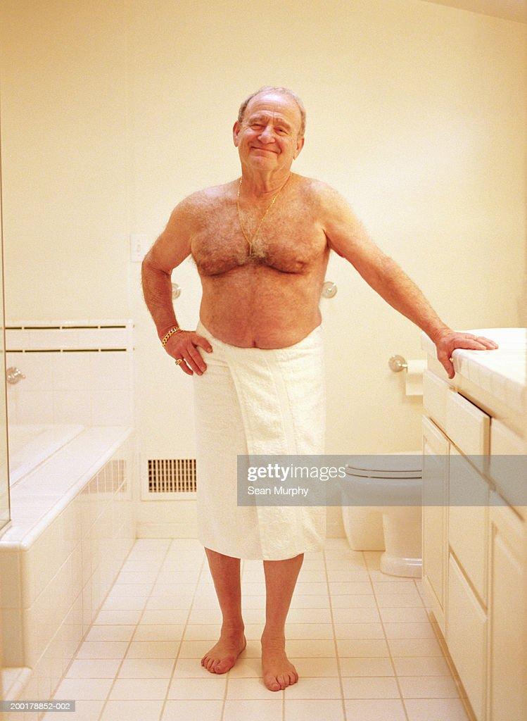 Senior man in towel, standing in bathroom, portrait : Stock Photo