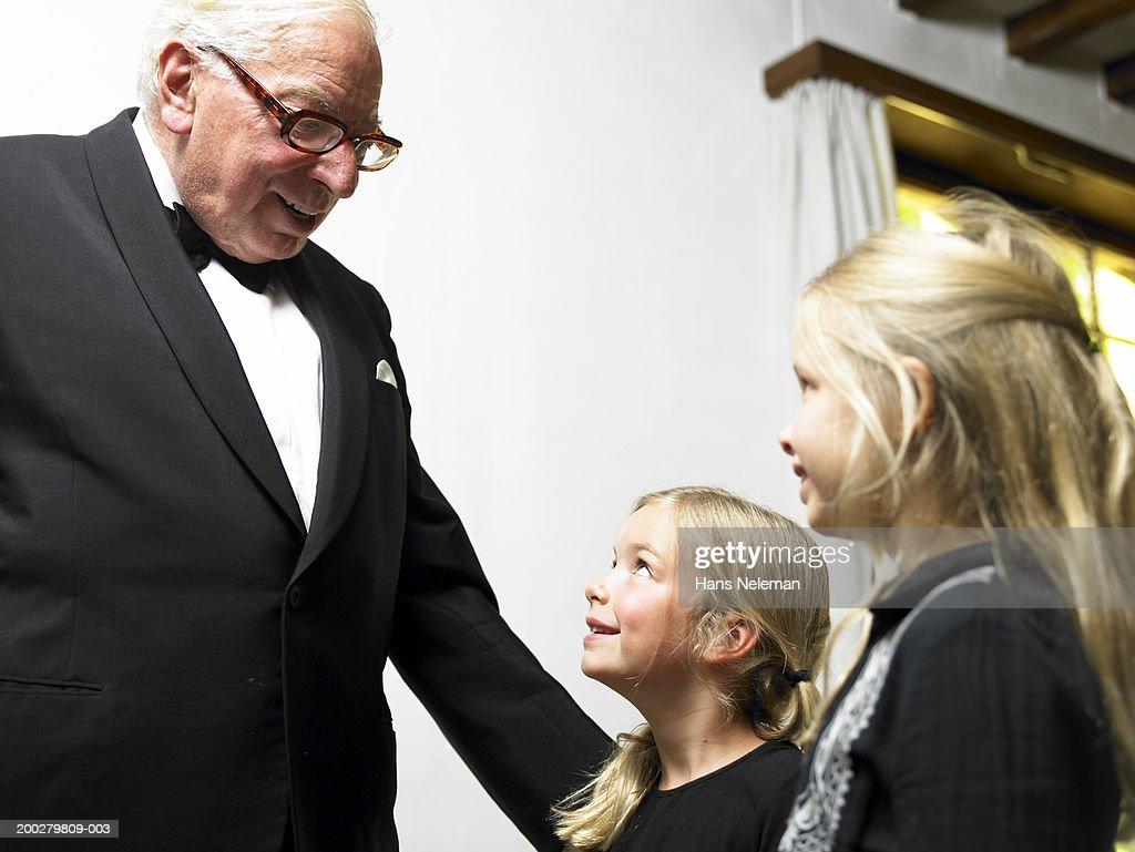 Senior man in tuxedo talking with girls (5-7), smiling, side view : Stock Photo