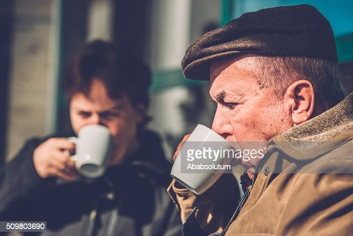 Senior Man in Wheelchair and Grandson Having Coffee, Europe