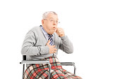 Senior man in wheelchair choking isolated on white background