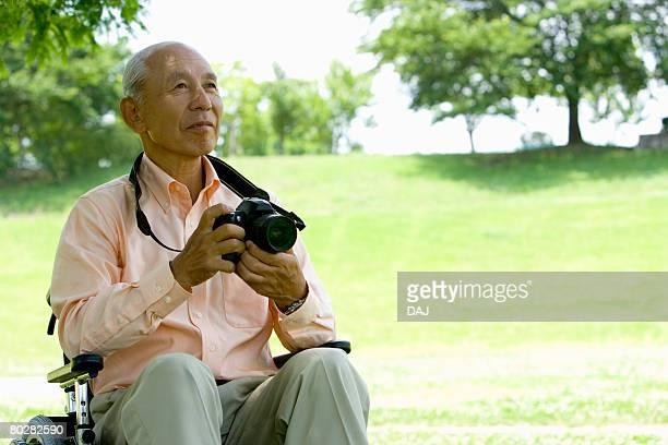 Senior man in wheelchair holding a camera