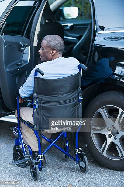 Senior man in wheelchair next to car